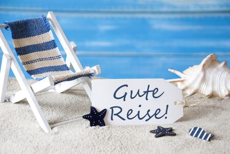 symbolized: Summer Label With German Text Gute Reise Means Good Trip. Blue Wooden Background. Card With Holiday Greetings. Beach Vacation Symbolized By Sand, Deck Chair And Shell. Stock Photo
