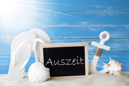 auszeit: Chalkboard With German Text Auszeit Means Downtime. Blue Wooden Background. Sunny Summer Card With Holiday Greetings. Beach Vacation Symbolized By Sand, Flip Flops, Anchor And Shell. Stock Photo