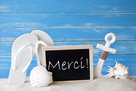 symbolized: Chalkboard With French Text Merci Means Thank You. Blue Wooden Background. Summer Card With Holiday Greetings. Beach Vacation Symbolized By Sand, Flip Flops, Anchor And Shell.