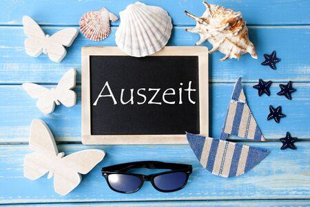 auszeit: Flat Lay Of Chalkboard On Blue Wooden Background. Nautical Summer Decoration As Holiday Greeting Card. German Text Auszeit Means Relax