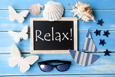 downtime: Flat Lay Of Chalkboard On Blue Wooden Background. Nautical Summer Decoration As Holiday Greeting Card.English Text Relax