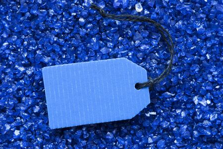 small stones: One Blue Label Or Tag With Black Ribbon On Blue And Purple Small Stones As Background. Copy Space Your Text Here Or Free Text For Advertisement Stock Photo