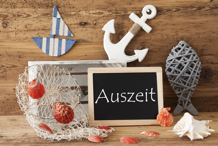 auszeit: Blackboard With Nautical Summer Decoration And Wooden Background. German Text Auszeit Means Relax. Fish, Anchor, Shells And Fishnet For Maritime Contex.