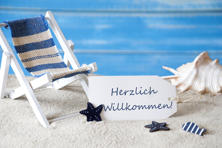 symbolized: Summer Label With German Text Herzlich Willkommen Means Welcome. Blue Wooden Background. Card With Holiday Greetings. Beach Vacation Symbolized By Sand, Deck Chair And Shell. Stock Photo