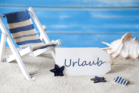 symbolized: Summer Label With German Text Urlaub Means Holiday Or Vacation. Blue Wooden Background. Card With Holiday Greetings. Beach Vacation Symbolized By Sand, Deck Chair And Shell. Stock Photo