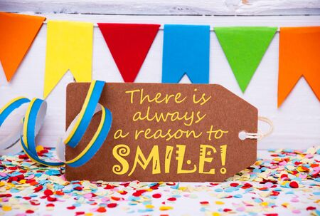 like english: Label With English Quote There Is Always A Reason To Smile. Party Decoration Like Streamer, Confetti And Bunting Flags. White Wooden Background With Vintage, Retro Or Rustic Syle