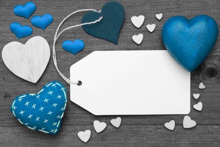 hot spot: Label With Blue Textile Hearts On Wooden Gray Background. Copy Space For Advertisement Or Your Free Text Here. Retro Or Vintage Style. Black And White Image With Colored Hot Spot. Stock Photo