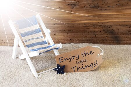 downtime: Sunny Summer Label With Sand And Aged Wooden Background. English Quote Enjoy The Little Things. Deck Chair For Holiday Or Vacation Feeling.