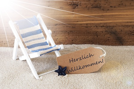 willkommen: Sunny Summer Label With Sand And Aged Wooden Background. German Text Herzlich Willkommen Means Welcome. Deck Chair For Holiday Or Vacation Feeling. Stock Photo