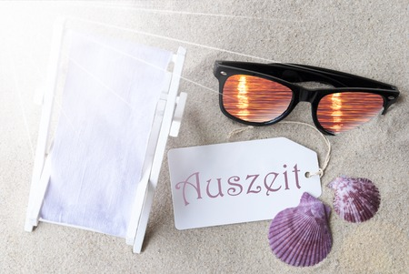 auszeit: Sunny Summer Label With German Text Auszeit Means Relax. Flat Lay View. Summer Decoration With Deck Chair, Seashells And Sunglasses. Greeting Crad With Sand Background