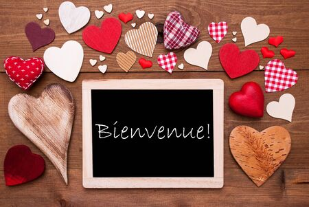 french text: Chalkboard With French Text Bienvenue Means Welcome. Many Red Textile Hearts. Wooden Background With Vintage, Rustic Or Retro Style. Stock Photo