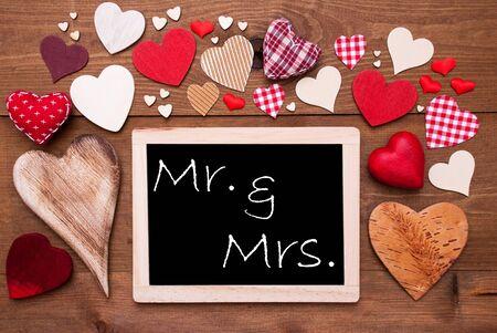 mrs: Pizarra con el texto Ingl�s Sr. y la Sra muchos corazones rojos textiles. Fondo de madera con la vendimia, r�stica o estilo retro. Foto de archivo