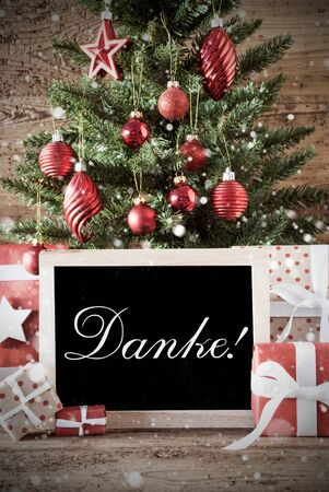 nostalgic: Nostalgic Christmas Card For Seasons Greetings. Christmas Tree With Balls. Gifts Or Presents In The Front Of Wooden Background. Chalkboard With German Text Danke Means Thank You