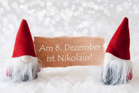 nikolaus: Christmas Greeting Card With Two Red Gnomes. Sparkling Bokeh Background With Snow. German Text Am 6. Dezember Ist Nikolaus Means Nicholas Day Stock Photo