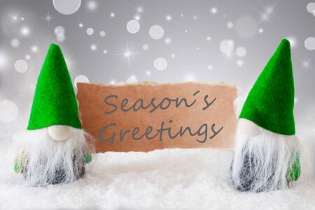 gnomos: Christmas Greeting Card With Two Green Gnomes. Sparkling Bokeh And Noble Silver Background With Snow. English Text Seasons Greetings