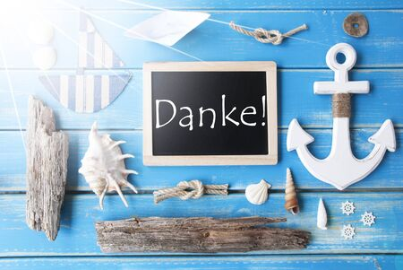 nautic: Flat Lay Of Chalkboard On Blue Wooden Background. Sunny Nautic Or Maritime Summer Decoration As Holiday Greeting Card. German Text Danke Means Thank You