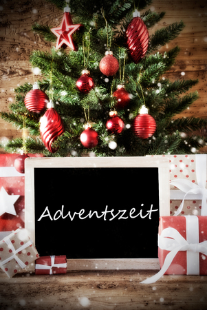 advent season: Christmas Card For Seasons Greetings. Christmas Tree With Balls. Gifts Or Presents In The Front Of Wooden Background. Chalkboard With German Text Adventszeit Means Advent Season Stock Photo