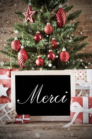 nostalgic christmas: Nostalgic Christmas Card For Seasons Greetings. Christmas Tree With Balls. Gifts Or Presents In The Front Of Wooden Background. Chalkboard With French Text Merci Means Thank You