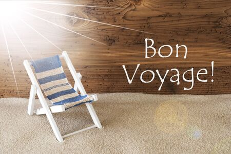 french text: Sunny Summer Greeting Card With Sand And Aged Wooden Background. French Text Bon Voyage Means Good Trip. Deck Chair For Holiday Or Vacation Feeling.