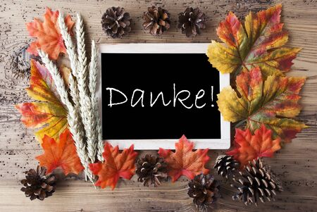 caes: Blackboard With Autumn Or Fall Decoration. Greeting Card For Seasons Greetings. Colorful Leaves, Fir Cone And Barley On Aged Wooden Background. German Text Danke Means Thank You Foto de archivo
