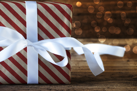 atmospheric: Macro Of Christmas Gift Or Present On Wooden Background. Copy Space For Advertisement. White Ribbon With Bow And Atmospheric Bokeh Effect Stock Photo