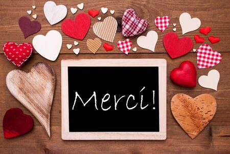merci: Chalkboard With French Text Merci Means Thank  You. Many Red Textile Hearts. Wooden Background With Vintage, Rustic Or Retro Style. Stock Photo