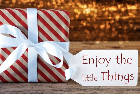 atmospheric: Macro Of Christmas Gift Or Present On Atmospheric Wooden Background. Card For Seasons Greetings, Best Wishes Or Congratulations. White Ribbon With Bow. English Quote Enjoy The Little Things