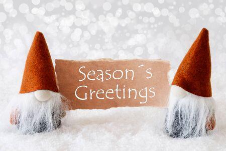 gnomos: Tarjeta de felicitación de la Navidad con dos gnomos de bronce. Espumoso bokeh de fondo con nieve. Inglés texto saludos de las estaciones