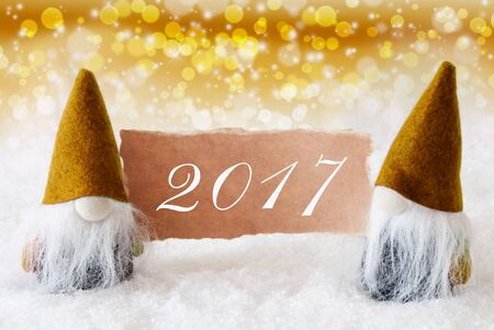 gnomos: Christmas Greeting Card With Two Golden Gnomes. Sparkling Bokeh And Noble Background With Snow. Text 2017