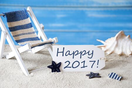 symbolized: Summer Label With English Text Happy 2017. Blue Wooden Background. Card With Holiday Greetings. Beach Vacation Symbolized By Sand, Deck Chair And Shell.