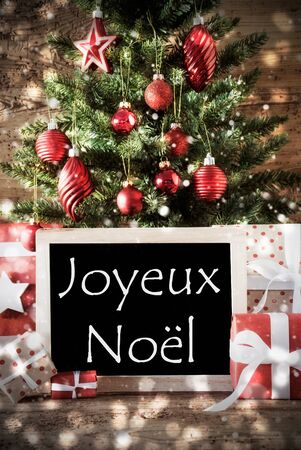 french text: Christmas Tree With Balls And Snowflakes. Gifts Or Presents In The Front Of Wooden Background With Bokeh Effect. Chalkboard With French Text Joyeux Noel Means Merry Christmas