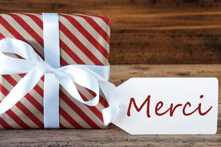 french text: Macro Of Christmas Gift Or Present On Wooden Background. Card For Seasons Greetings, Best Wishes Or Congratulations. White Ribbon With Bow. French Text Merci Means Thank You Stock Photo