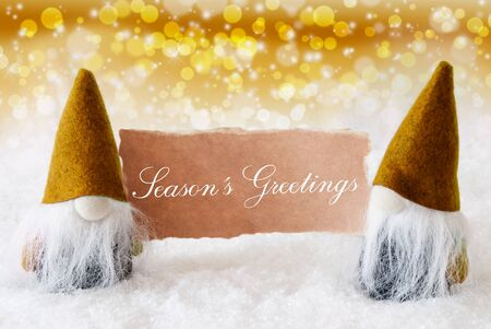 gnomos: Christmas Greeting Card With Two Golden Gnomes. Sparkling Bokeh And Noble Background With Snow. English Text Seasons Greetings