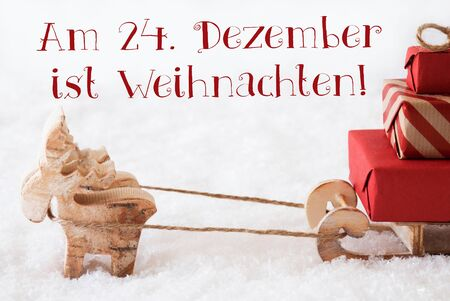 weihnachten: Moose Is Drawing A Sled With Red Gifts Or Presents In Snow. Christmas Card For Seasons Greetings. German Text Am 24. Dezember Ist Weihnachten Means Christmas Stock Photo