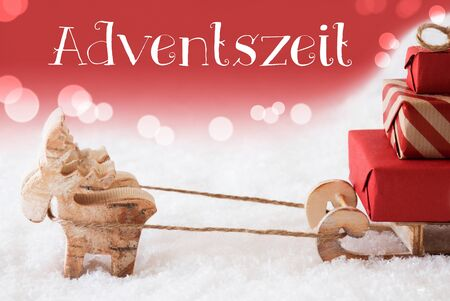 christmassy: Moose Is Drawing A Sled With Red Gifts Or Presents In Snow. Christmas Card For Seasons Greetings. Red Christmassy Background With Bokeh Effect. German Text Adventszeit Means Advent Season Stock Photo