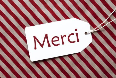 french text: One Label On A Red And Brown Striped Wrapping Paper. Textured Background. Tag With Ribbon. French Text Merci Means Thank You