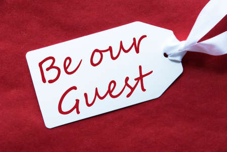 english text: One White Label On A Red Textured Background. Tag With Ribbon. English Text Be Our Guest