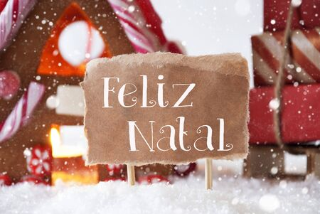 natal: Gingerbread House In Snowy Scenery As Christmas Decoration. Sleigh With Christmas Gifts Or Presents And Snowflakes. Label With Portuguese Text Feliz Natal Means Merry Christmas