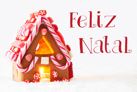 Gingerbread House In Snowy Scenery As Christmas Decoration With White Background. Candlelight For Romantic Atmosphere. Portuguese Text Felzi Natal Means Merry Christmas
