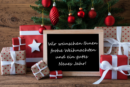 frohe: Colorful Christmas Card For Seasons Greetings. Christmas Tree With Red Balls. Gifts Or Presents In The Front Of Wooden Background. Chalkboard With German Text Frohe Weihnachten Und Ein Gutes Neues Jahr Means Merry Christmas And Happy New Year Stock Photo