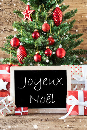 french text: Colorful Christmas Card For Seasons Greetings. Tree With Balls And Snowflakes. Gifts Or Presents In The Front Of Wooden Background. Chalkboard With French Text Joyeux Noel Means Merry Christmas Stock Photo
