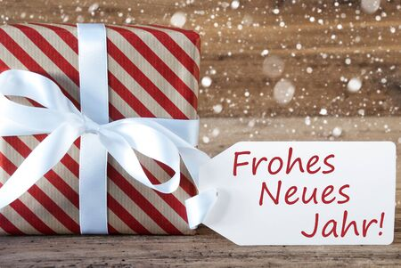 jahr: Christmas Gift Or Present On Wooden Background With Snowflakes. Card For Seasons Greetings. White Ribbon With Bow. German Text Frohes Neues Jahr Means Happy New Year Stock Photo