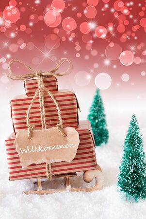 willkommen: Vertical Image Of Sleigh Or Sled With Christmas Gifts Or Presents. Snowy Scenery With Snow And Trees. Red Sparkling Background With Bokeh. Label With German Text Willkommen Means Welcome