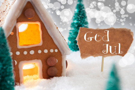 house of god: Gingerbread House In Snowy Scenery As Christmas Decoration. Trees And Candlelight For Romantic Atmosphere. Silver Background With Bokeh Effect. French Text God Jul Means Merry Christmas
