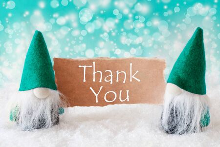 english text: Christmas Greeting Card With Two Turqoise Gnomes. Sparkling Bokeh Background With Snow. English Text Thank You