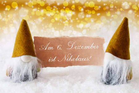 nikolaus: Christmas Greeting Card With Two Golden Gnomes. Sparkling Bokeh And Noble Background With Snow. German Text Am 6. Dezember Ist Nikolaus Means Nicholas Day