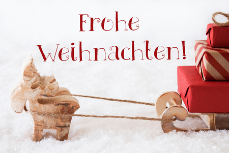 weihnachten: Moose Is Drawing A Sled With Red Gifts Or Presents In Snow. Christmas Card For Seasons Greetings. German Text Frohe Weihnachten Means Merry Christmas Stock Photo