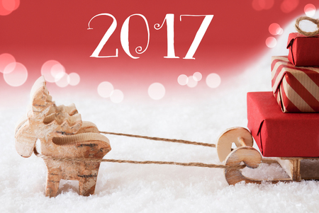 christmassy: Moose Is Drawing A Sled With Red Gifts Or Presents In Snow. Christmas Card For Seasons Greetings. Red Christmassy Background With Bokeh Effect. English Text 2017 For Happy New Year Stock Photo