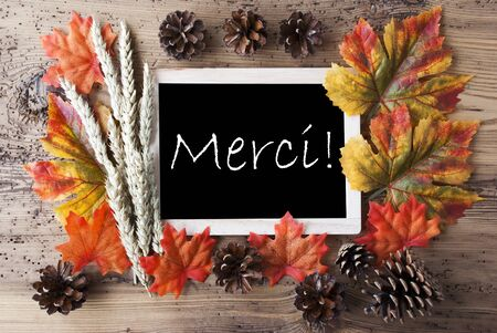 caes: Blackboard With Autumn Or Fall Decoration. Greeting Card For Seasons Greetings. Colorful Leaves, Fir Cone And Barley On Aged Wooden Background. French Text Merci Means Thank You Foto de archivo