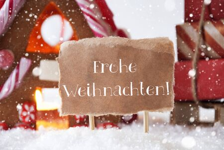 frohe: Gingerbread House In Snowy Scenery As Christmas Decoration. Sleigh With Christmas Gifts Or Presents And Snowflakes. Label With German Text Frohe Weihnachten Means Merry Christmas